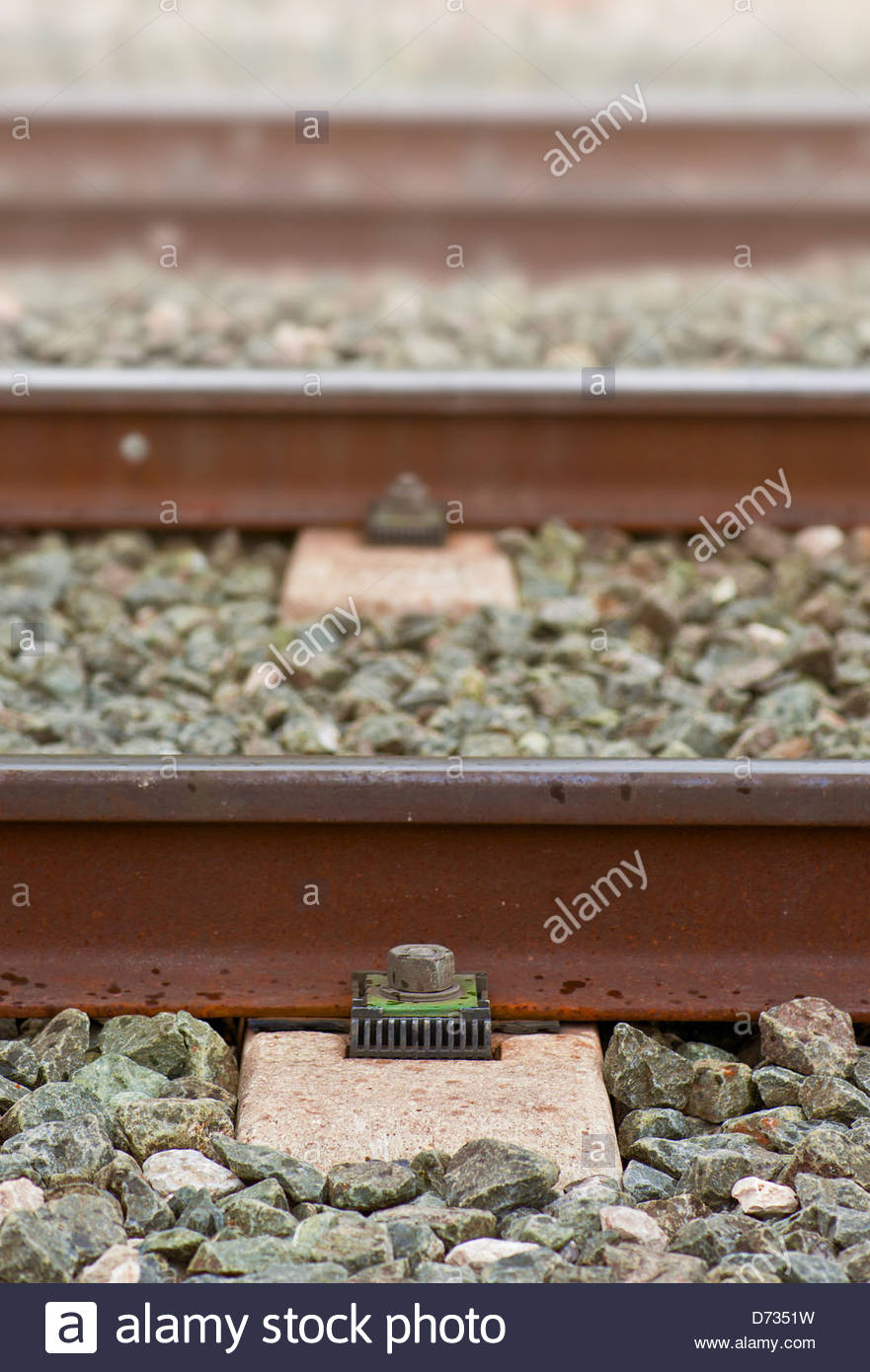 train tracks resting on a stone base - Stock Image
