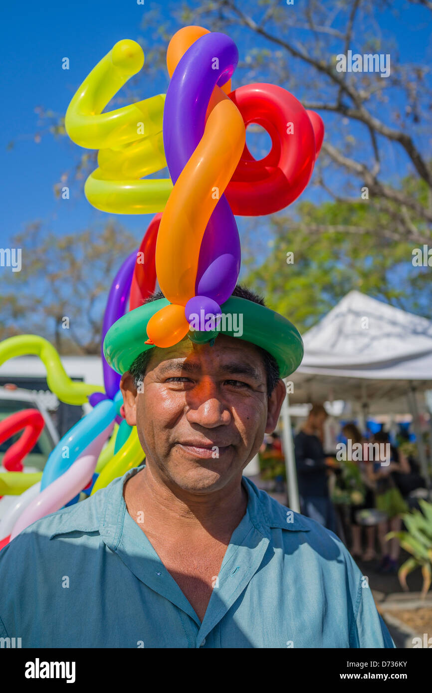 A balloon vendor who creates balloon art by tying them together wears one of his balloon creations on his head. - Stock Image