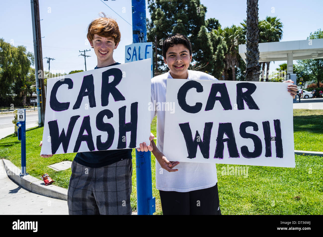 Two high school students, trying to get business, hold up signs that read 'Car Wash' at a busy intersection. - Stock Image