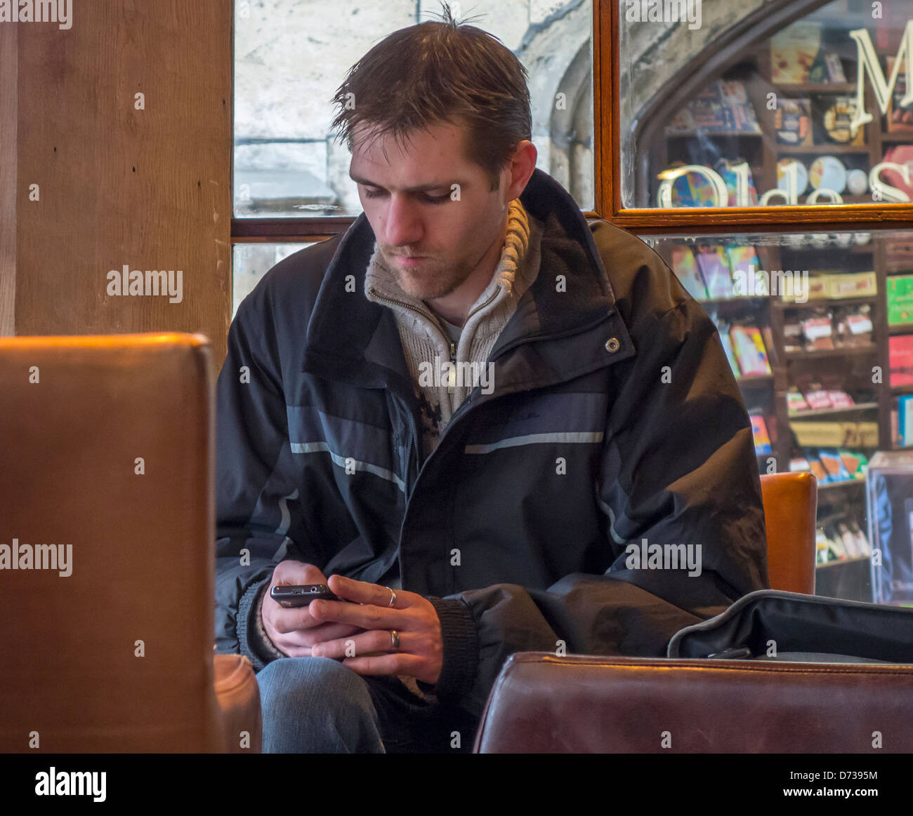 Man texting in coffee shop using mobile phone - Stock Image