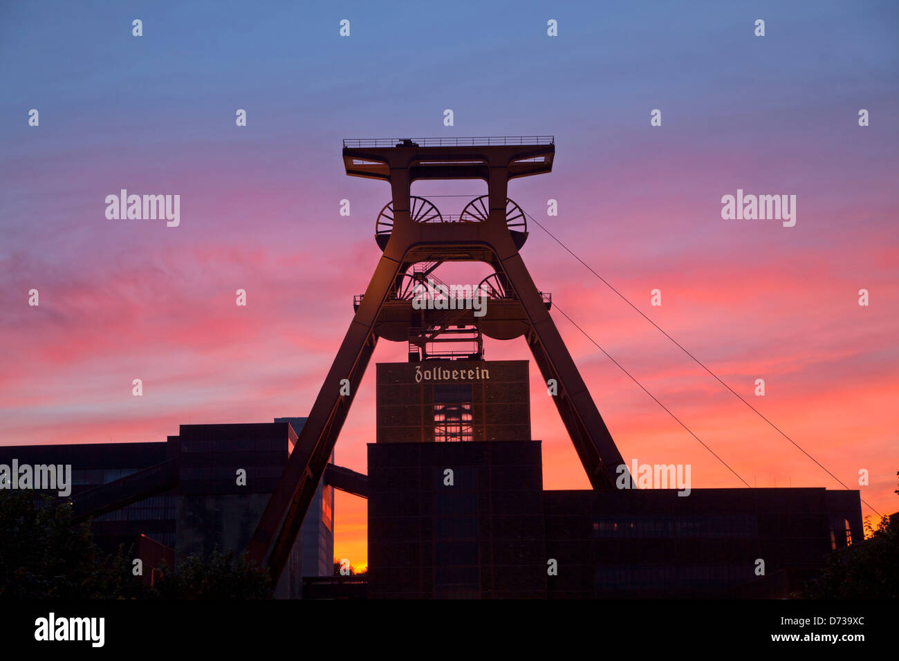 colourful sunset at the winding tower of shaft 12 at Zollverein Coal Mine Industrial Complex in Essen, North Rhine - Stock Image