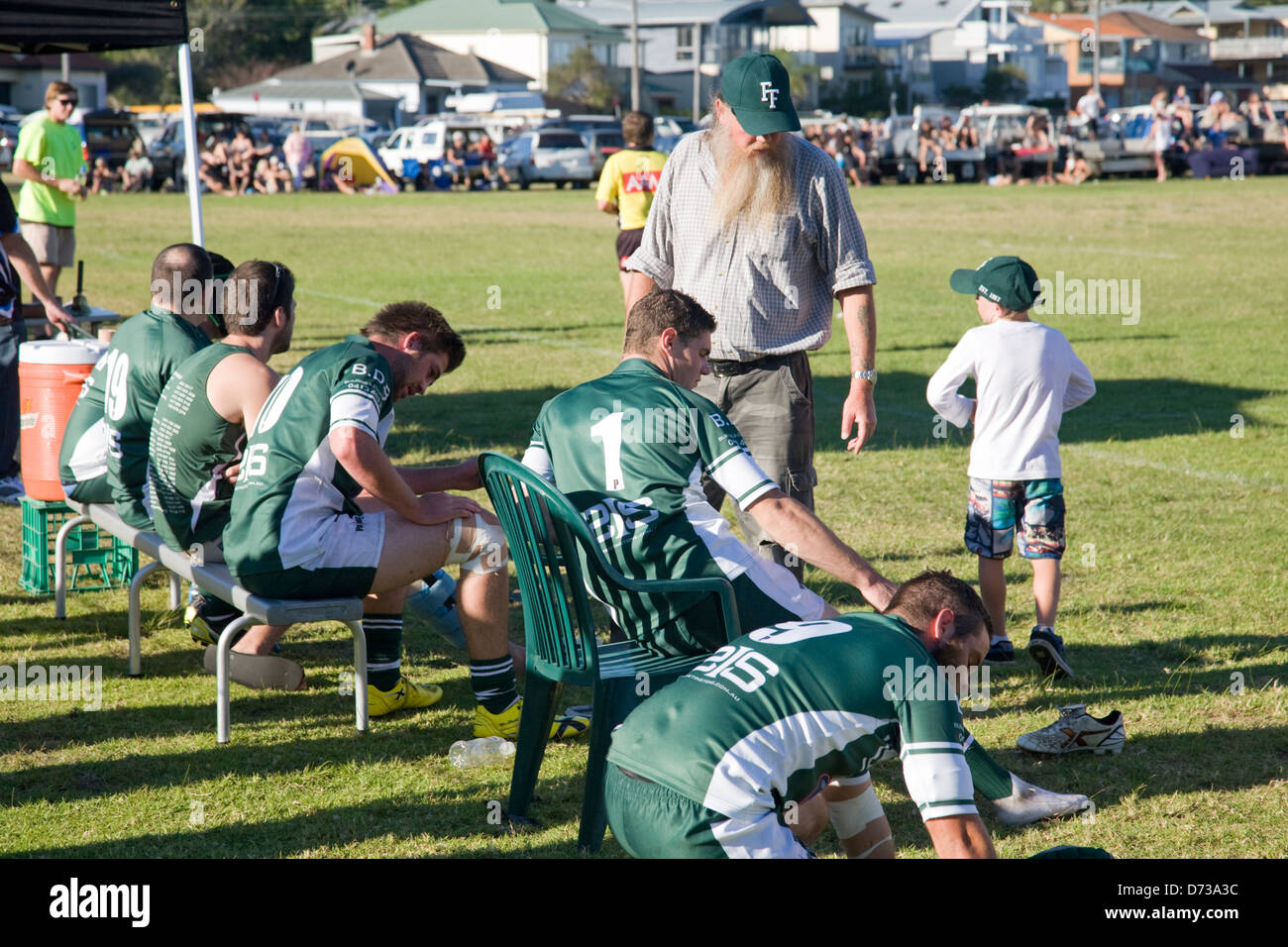 australian rugby league game being played in Sydney, players substitutes sitting beside the touchline - Stock Image