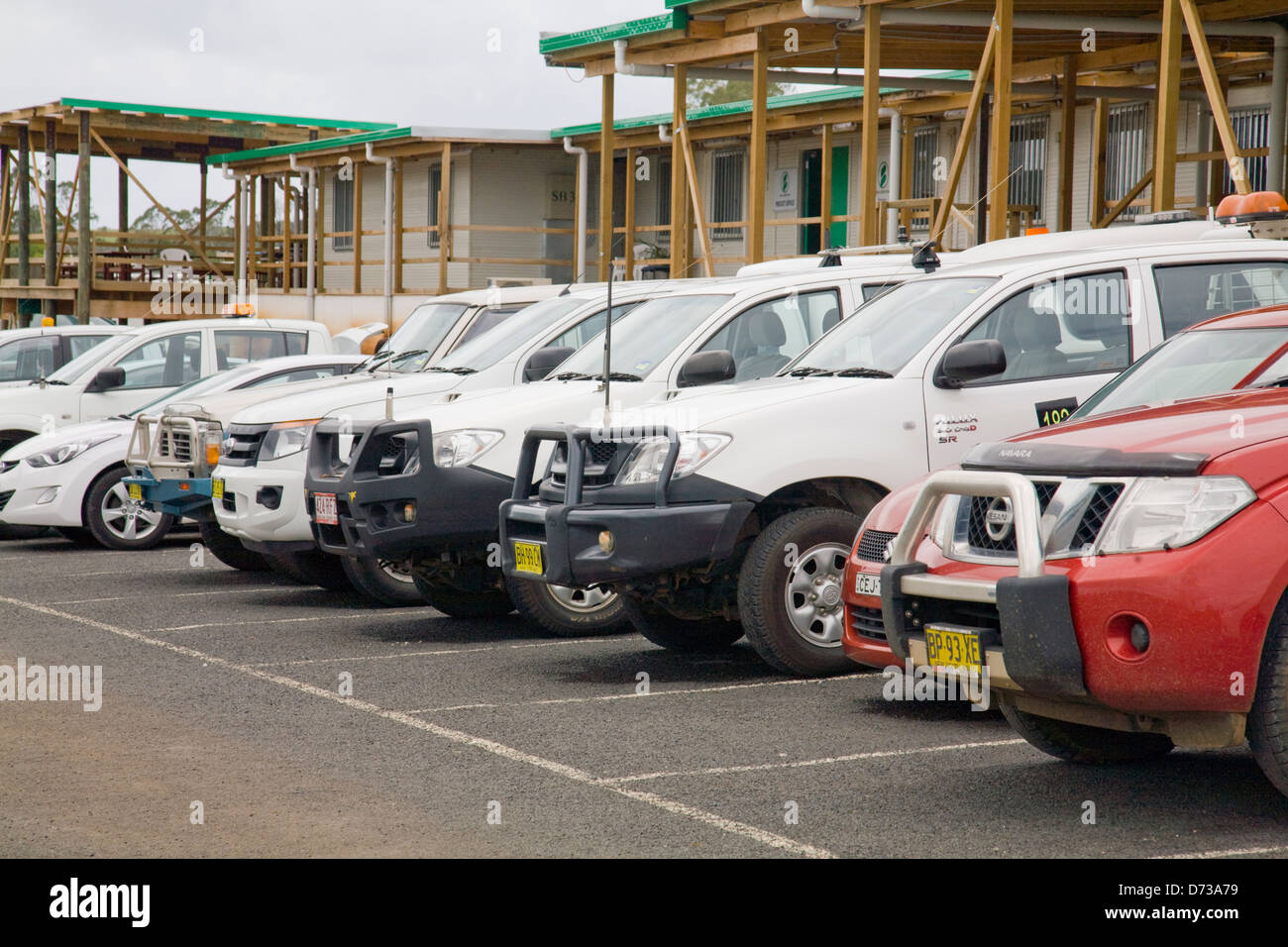 row of utes parked in a construction site compound Stock Photo