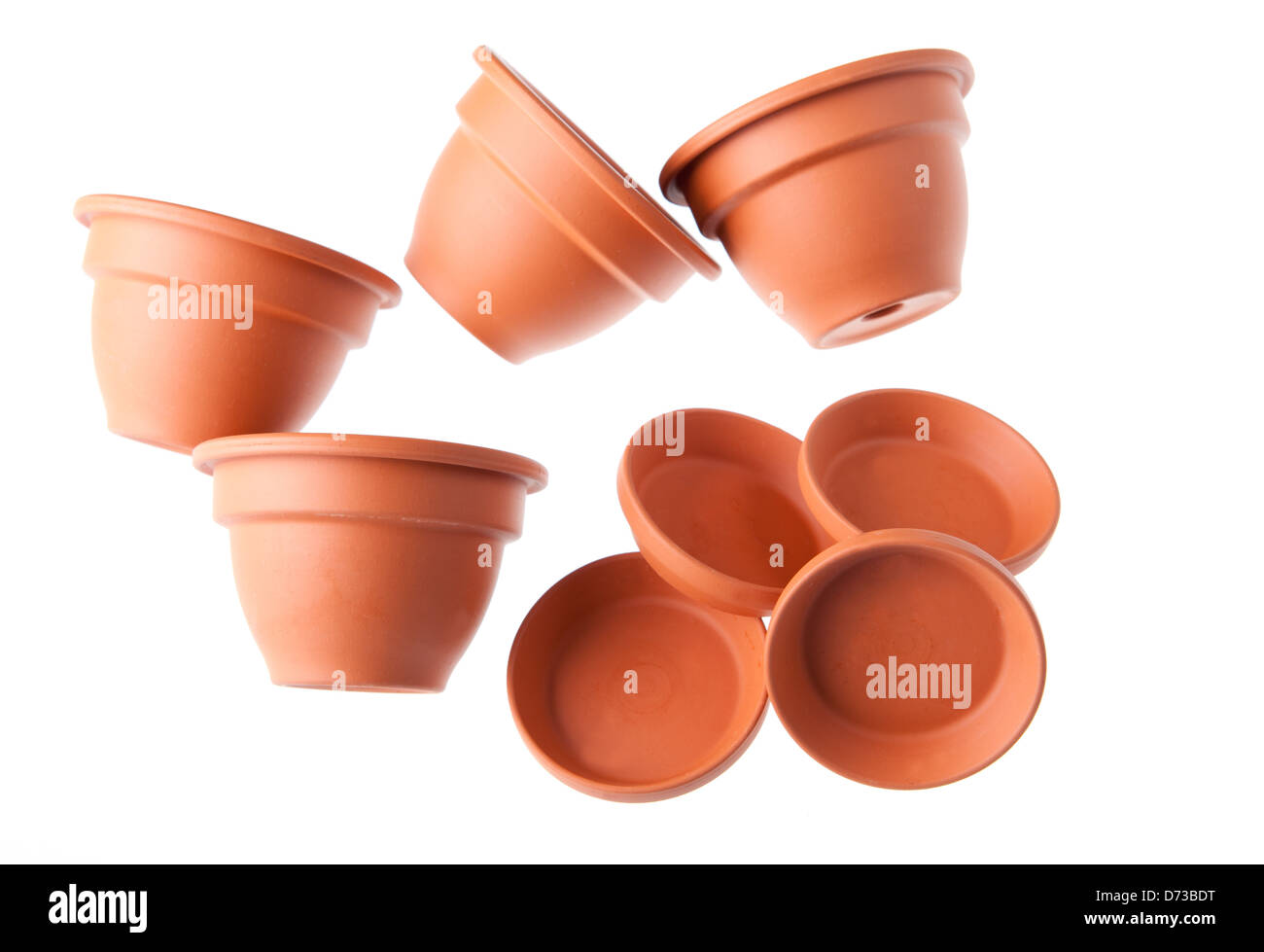 Four scattered clay flowerpots with saucers - Stock Image