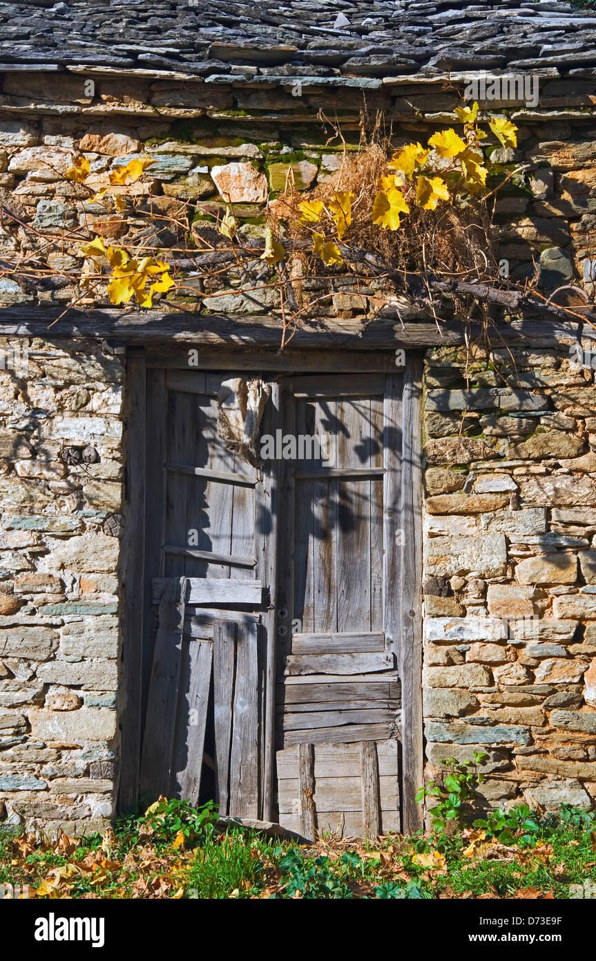 Ramshackle wooden door in old stone house front - Stock Image