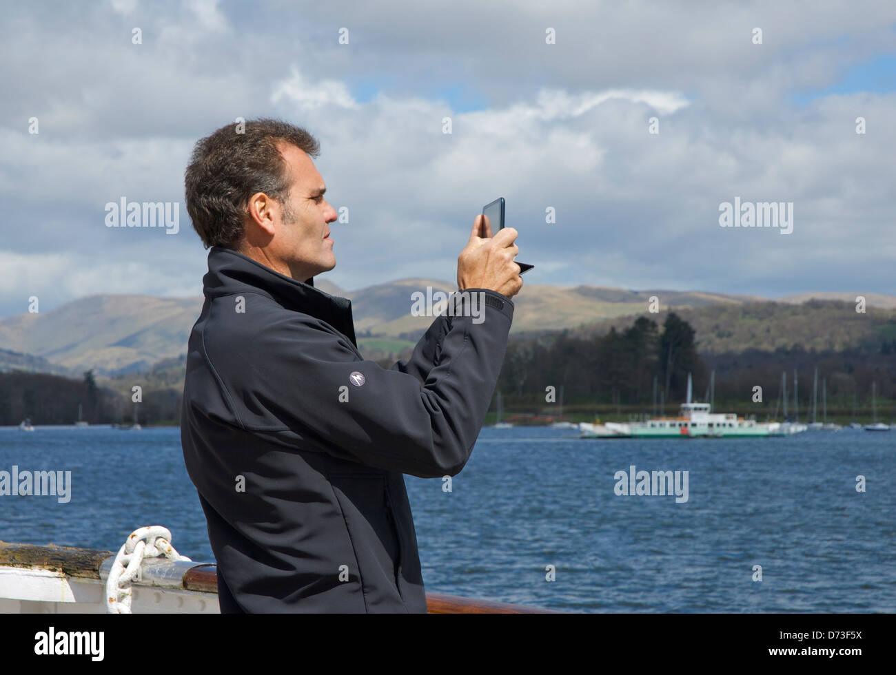 Man taking photographs with his iPad, Lake Windermere, Lake District National Park, Cumbria, England UK - Stock Image
