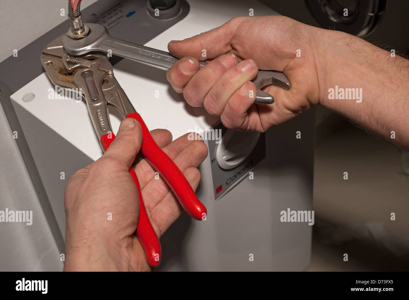 Berlin, Germany, a craftsman screwed to the supply of a water heater - Stock Image