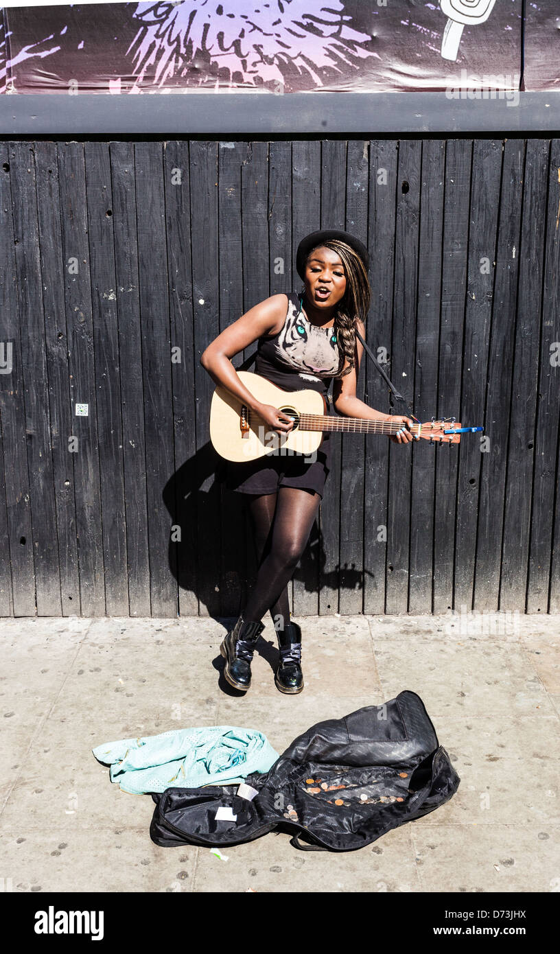 Portrait of a trendy, young, black female busker playing guitar and singing, Camden, London, England, UK - Stock Image