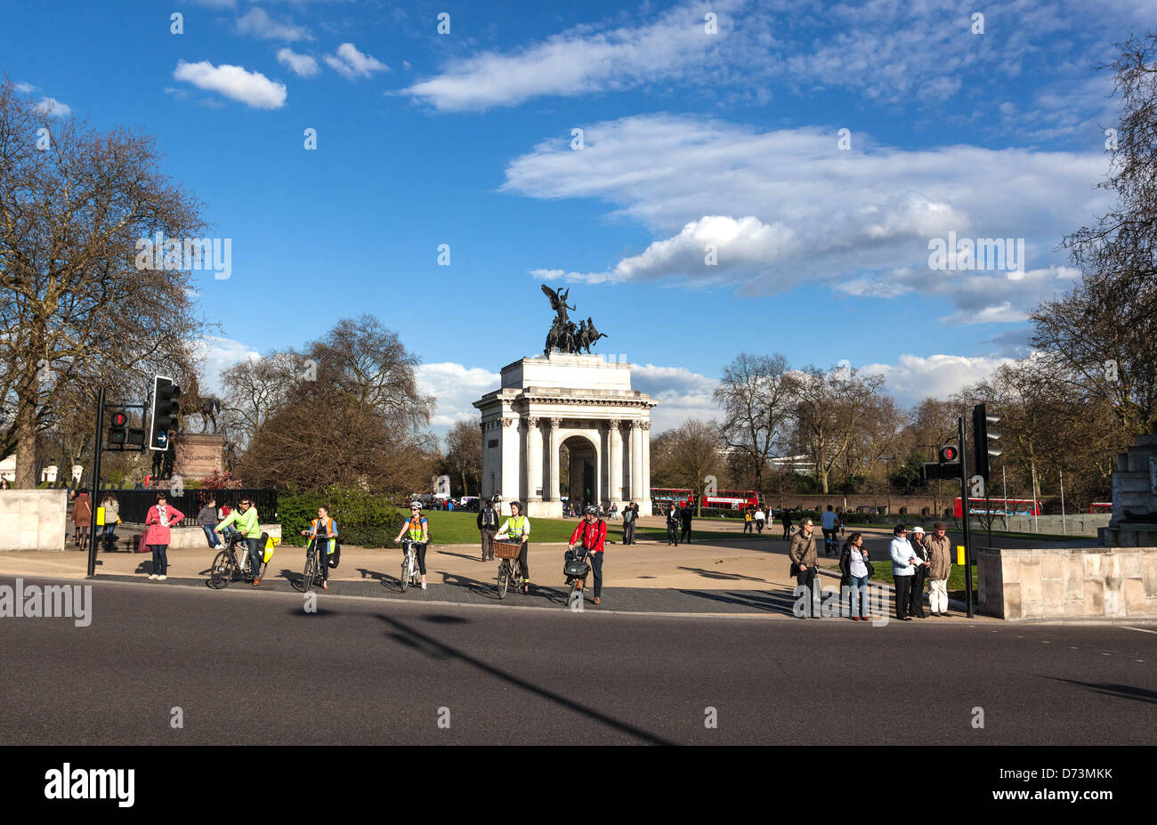 Cyclist and pedestrians waiting to cross the road at Hyde Park Corner, London, England, UK - Stock Image