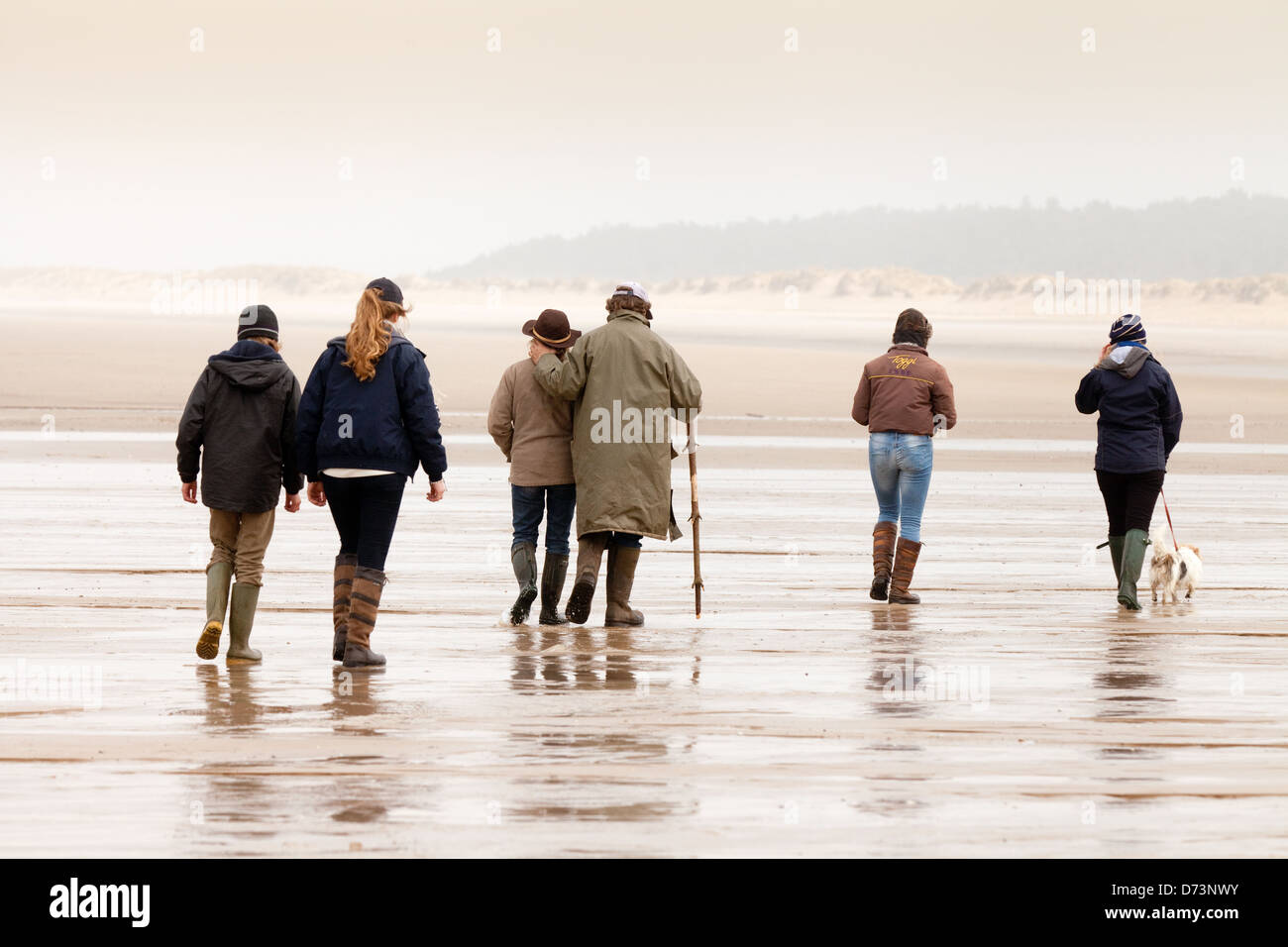 A group of people walking on the beach, seen from the rear, Holkham Beach, North Norfolk, UK - Stock Image