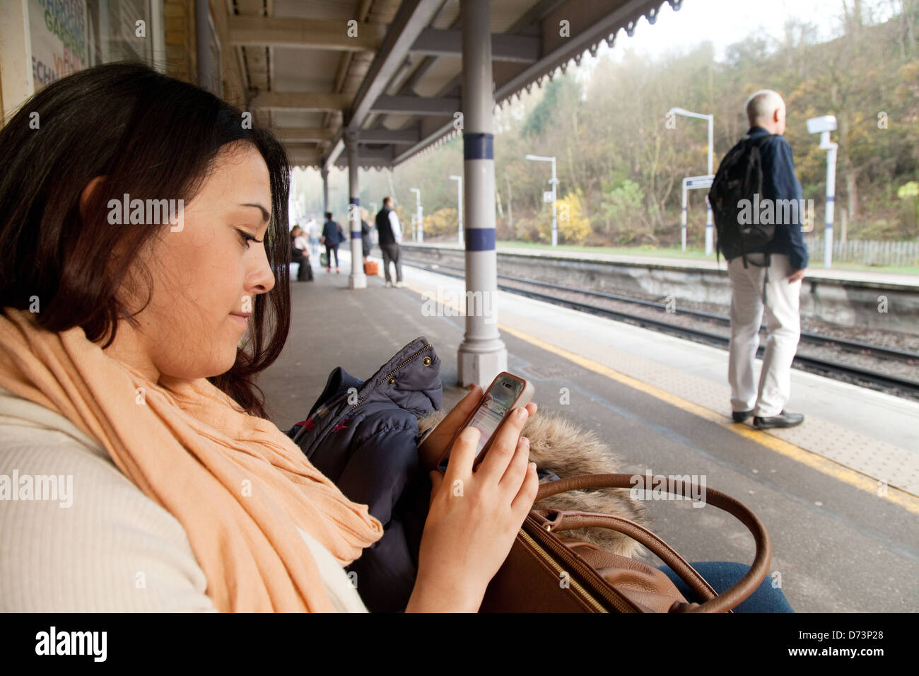 A young woman using her mobile phone on a station platform waiting for a train, London UK - Stock Image
