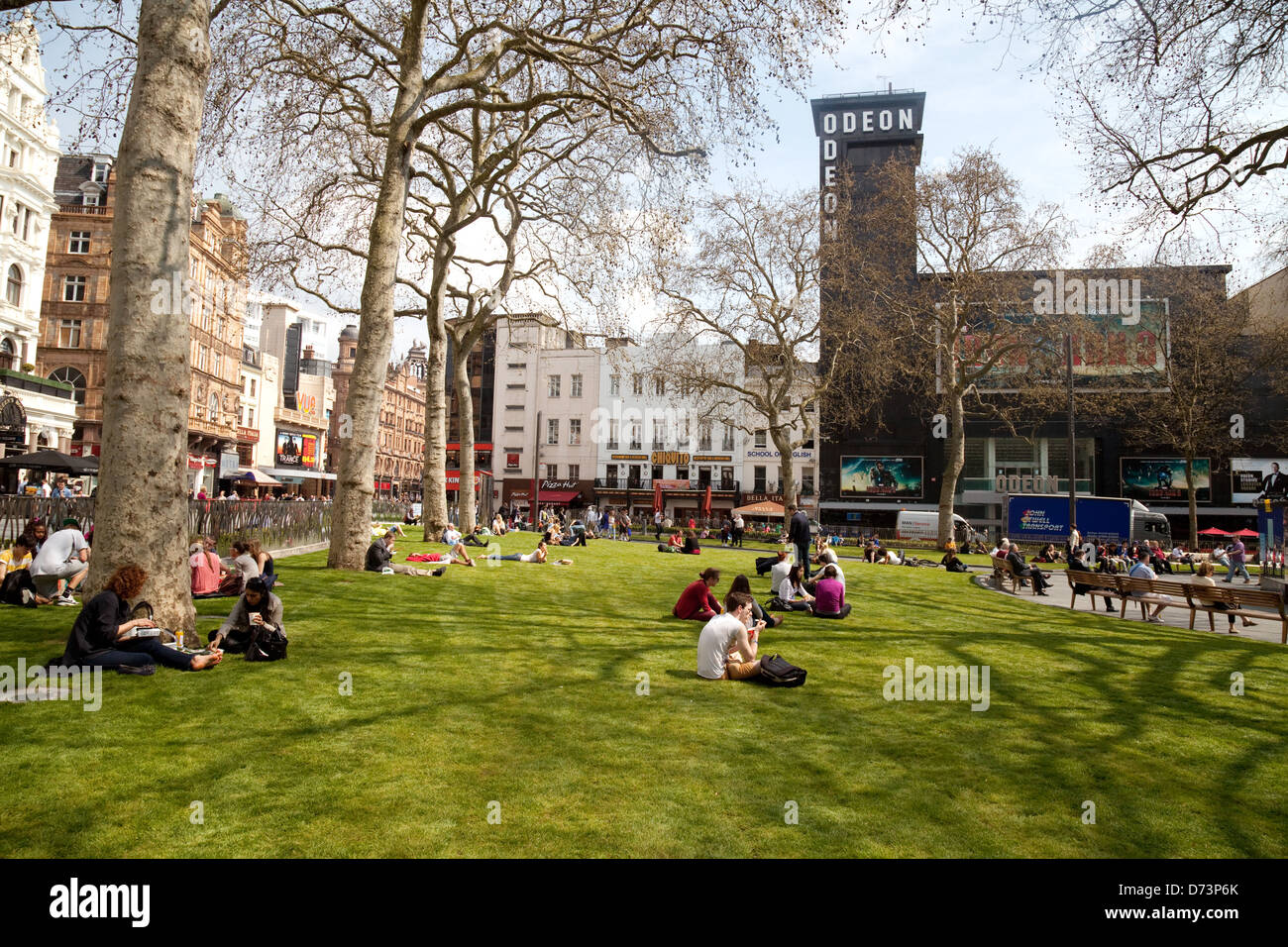 People sitting on the grass on a sunny day, Leicester Square Central London WC2, UK - Stock Image