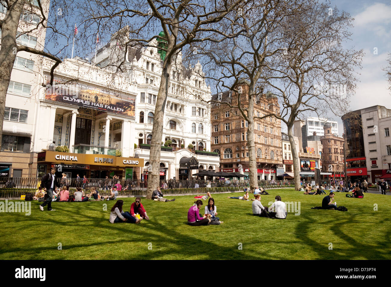 People sitting enjoying the sunshine in spring, Leicester Square, Central London WC2, UK Stock Photo