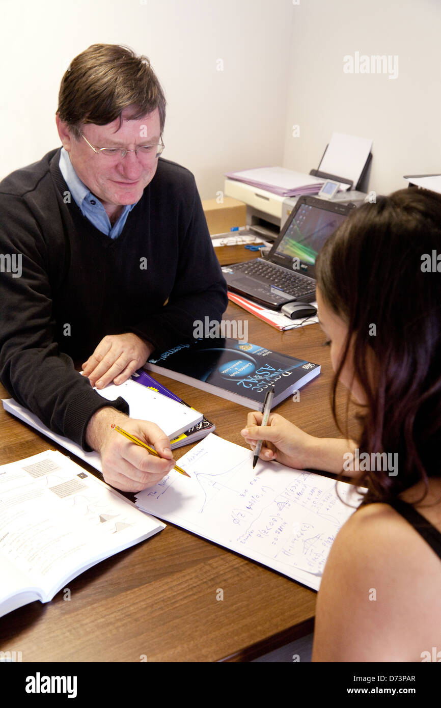 A student having extra private one to one maths tuition with a tutor, UK - Stock Image