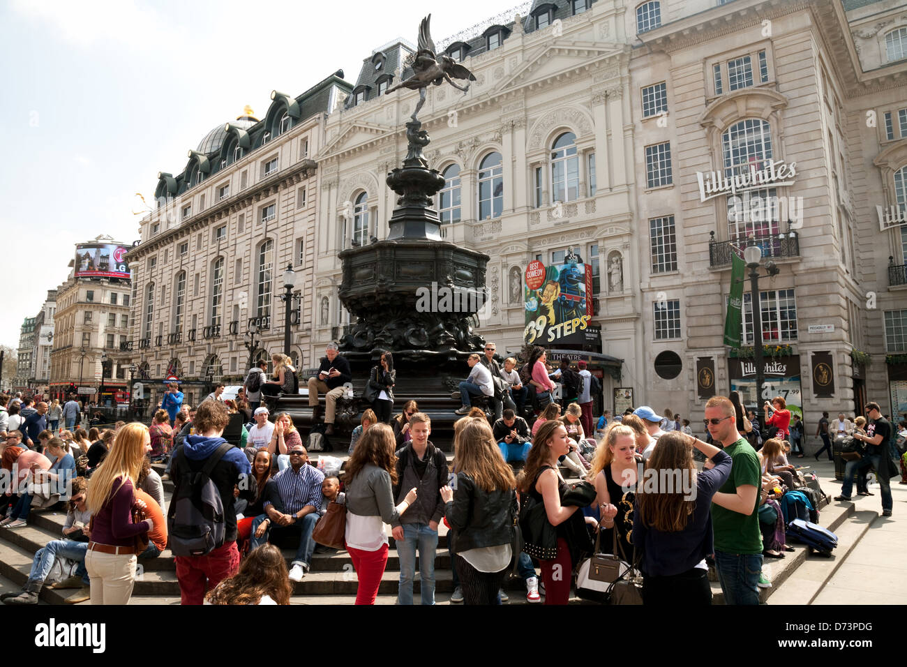 Crowd of tourists sitting round the statue of Eros, Piccadilly Circus, Central London W1, UK - Stock Image