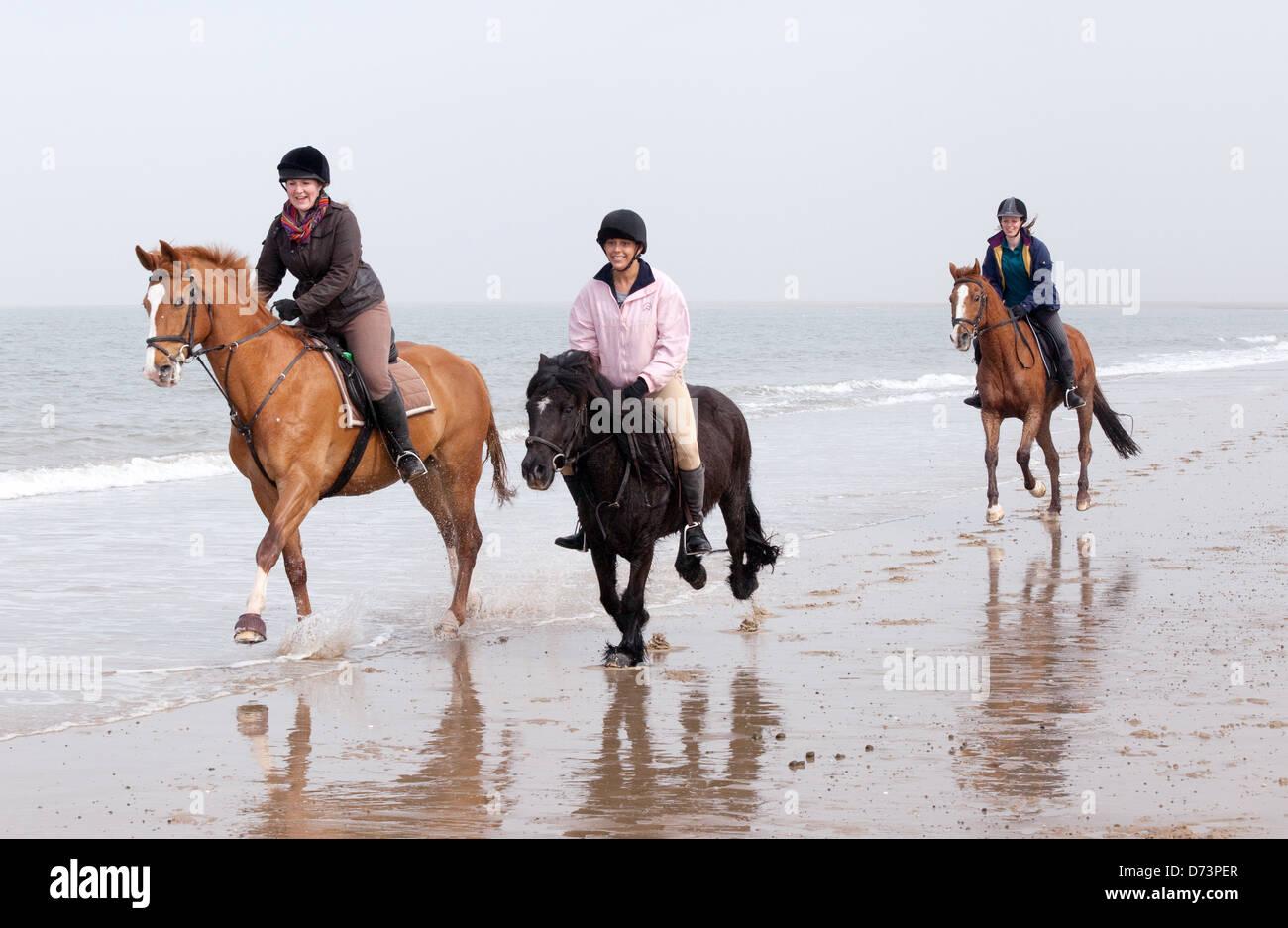 Three girls riding their horses, galloping on Holkham Beach, north Norfolk Coast, East Anglia UK - Stock Image
