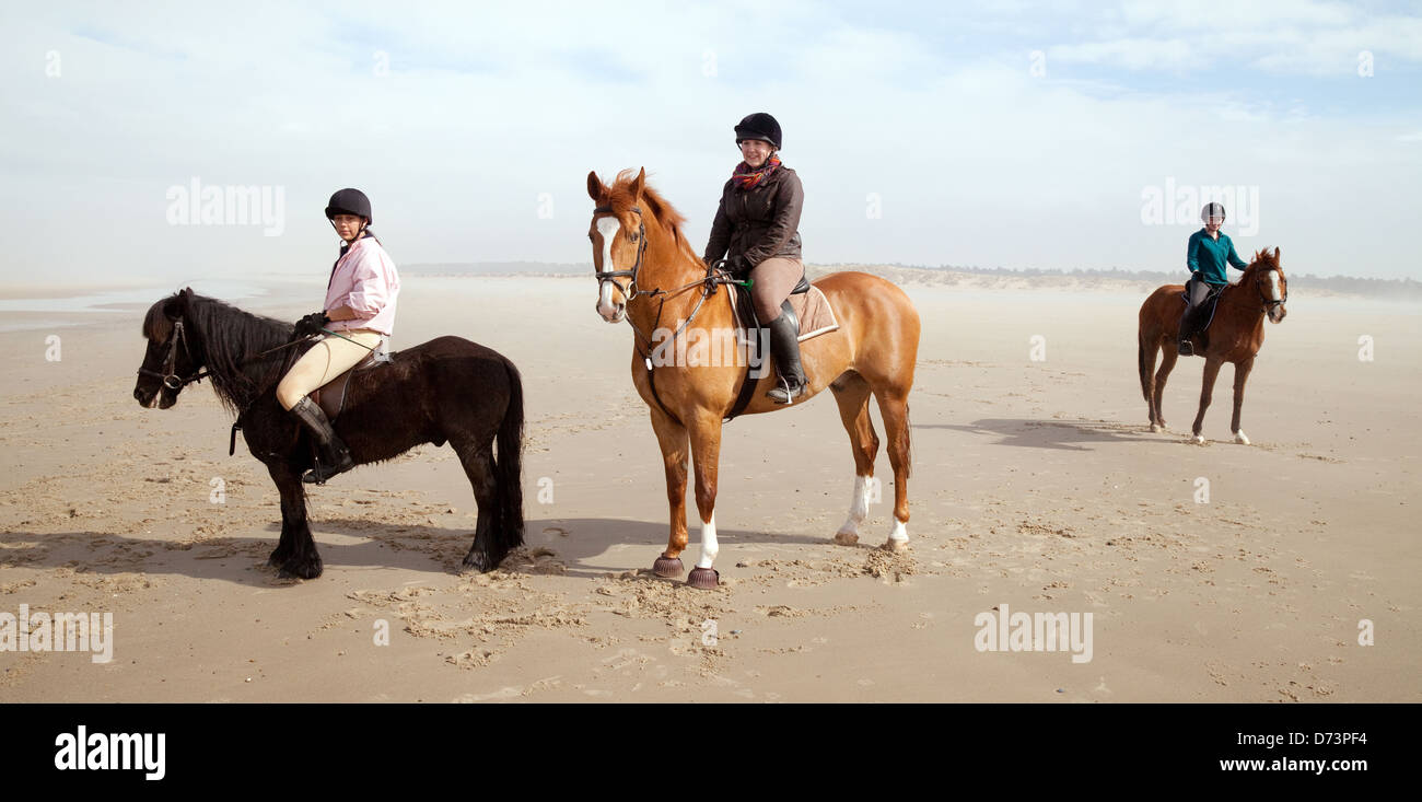 Three young women riding  horses at Holkham beach in spring, North Norfolk coast, UK - Stock Image