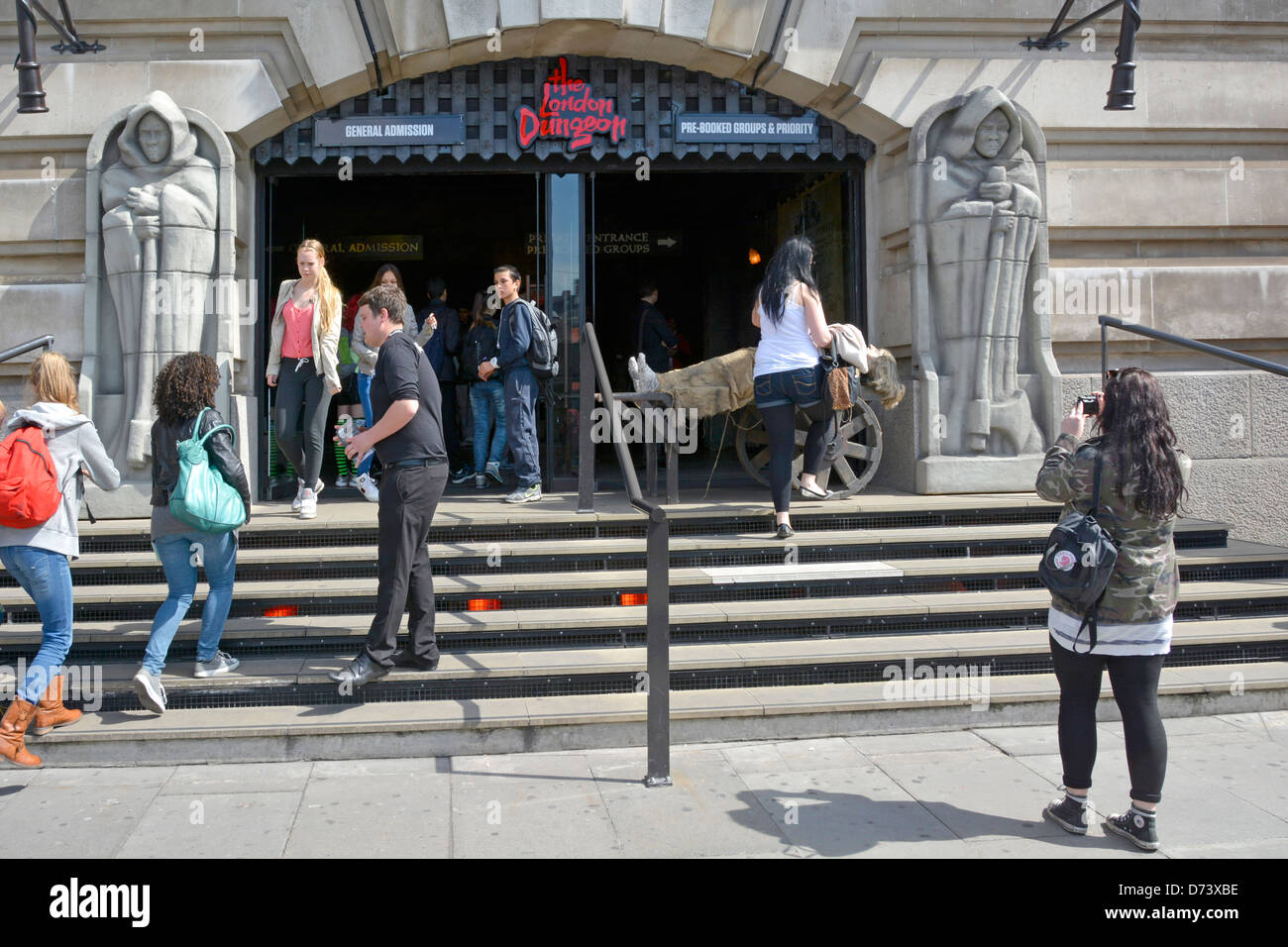 Tourists outside the New London Dungeon entrance on the South Bank run by Merlin Entertainments attractions - Stock Image
