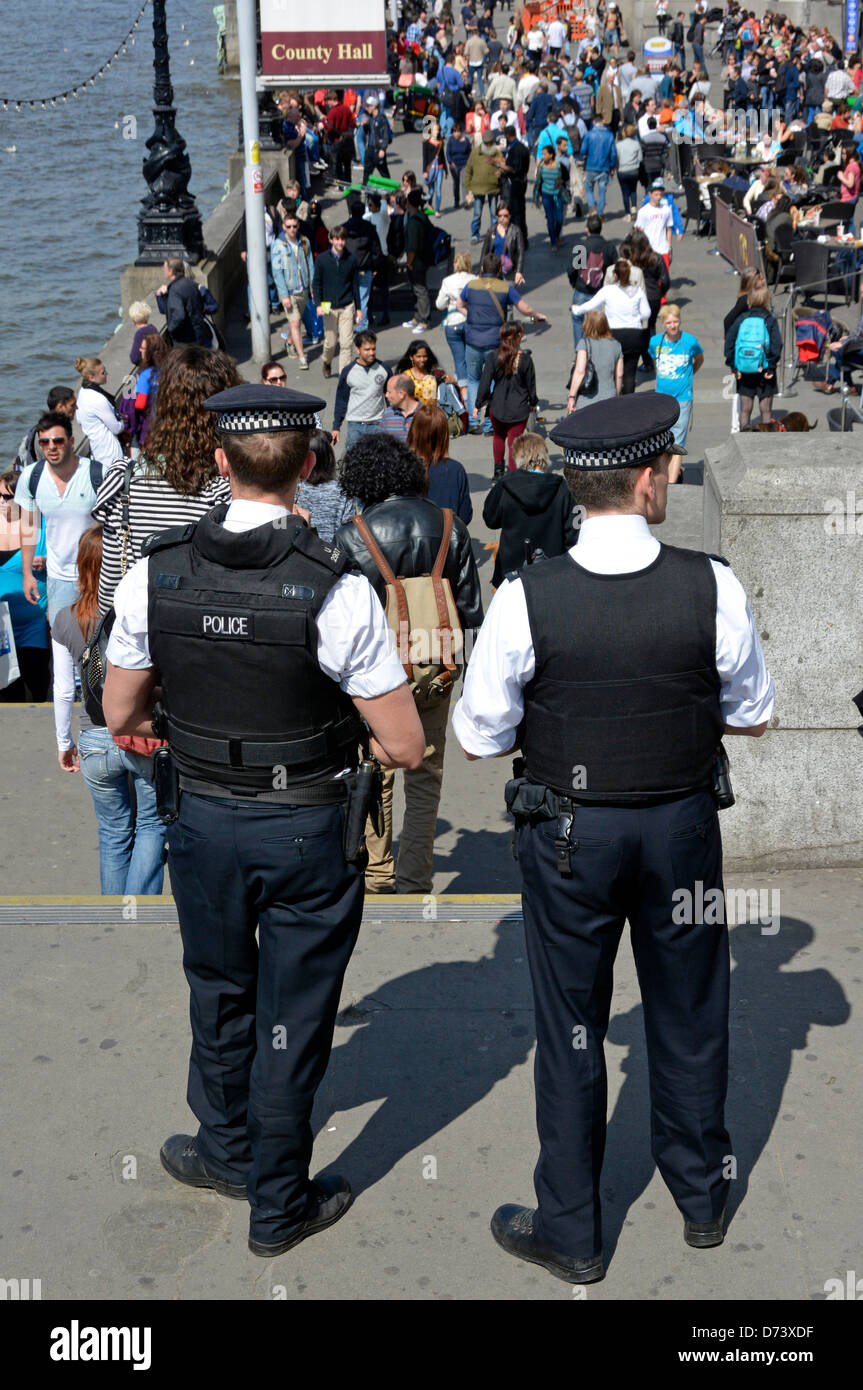 Metropolitan police officers watching crowds of tourists on County Hall riverside south bank - Stock Image