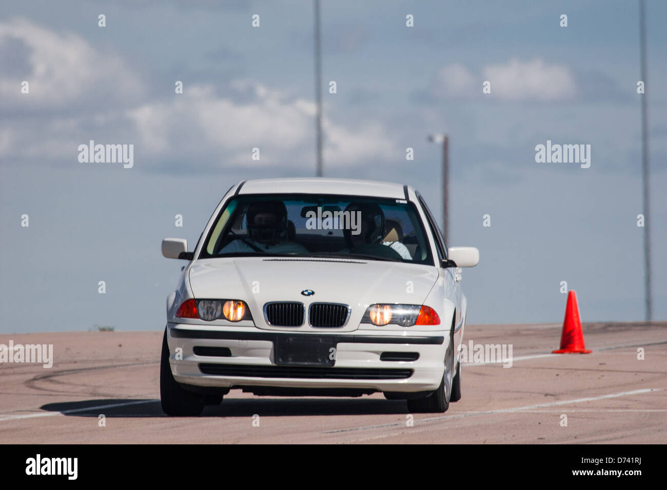 A 2001 White BMW 325 xi in an autocross race at a regional Sports Car Club of America (SCCA) event - Stock Image