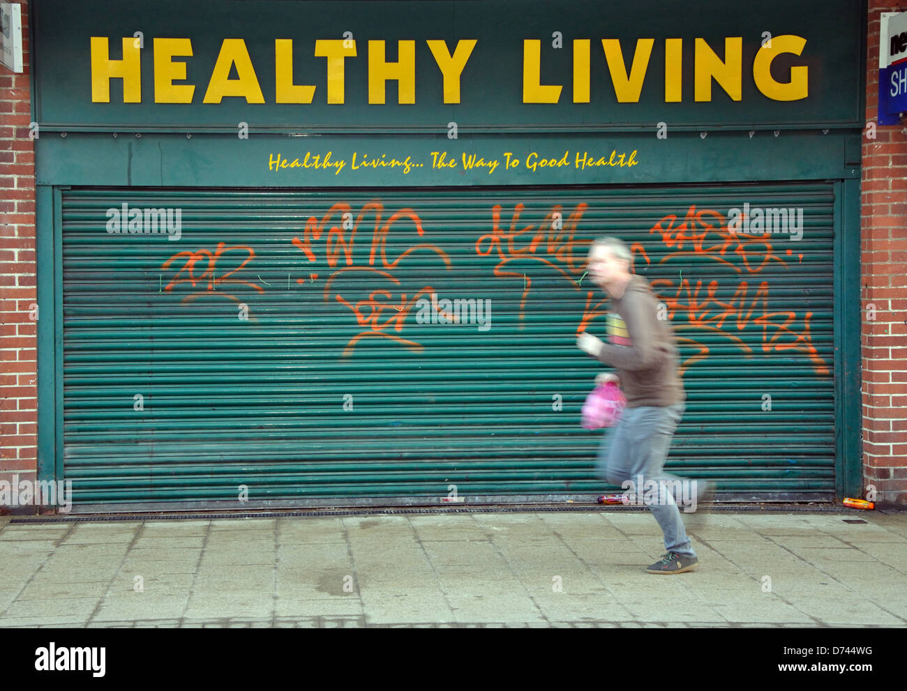 man jogging past closed Healthy Living shop, Bell Street, Wigston, Leicester, England, UK - Stock Image