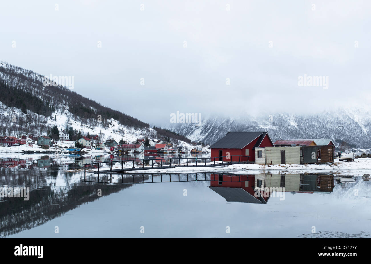 Reflections of houses in the perfectly still water of a bay in Norway - Stock Image