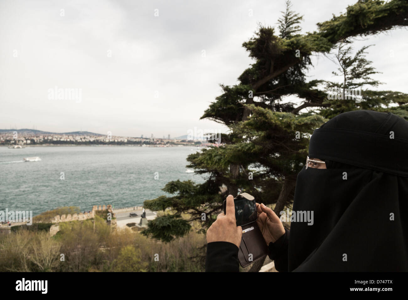 Muslim woman wearing a Burka take photos from the Topkapi palace area. - Stock Image