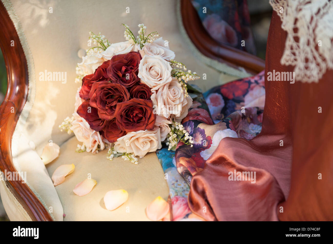 Bouquet of red and pink roses on an old fashioned high back chair - Stock Image