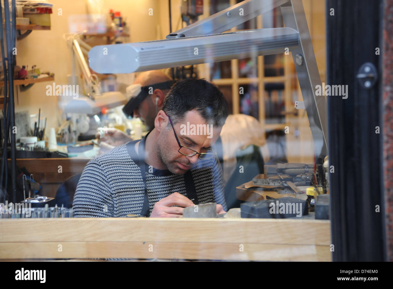 Jeweller at work in a shop window in Piccadilly London W1 UK - Stock Image