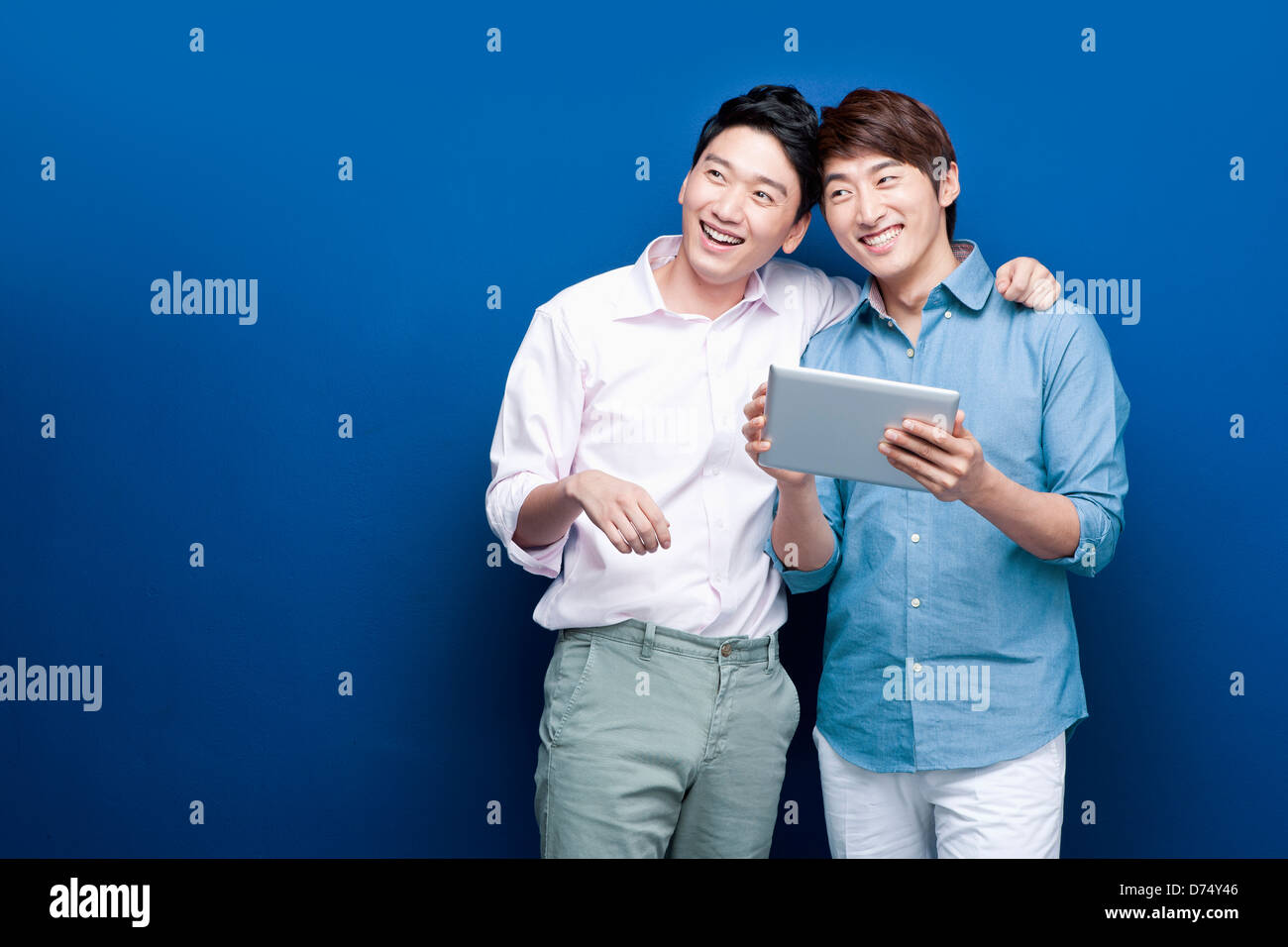two men in shirts sharing tablet PC - Stock Image