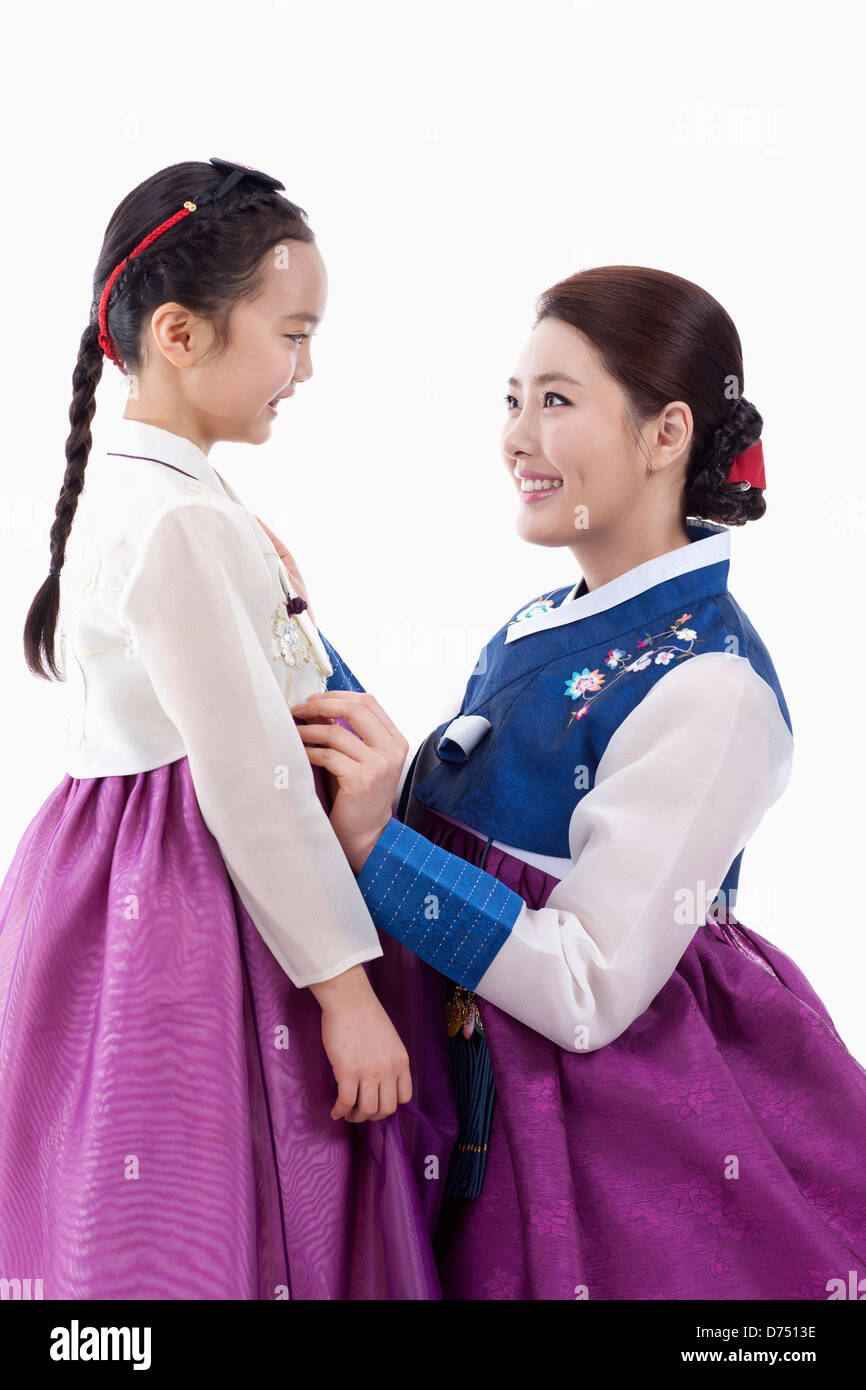 f57d7cc0d mother in Korean traditional costume fixing daughter's costume - Stock Image