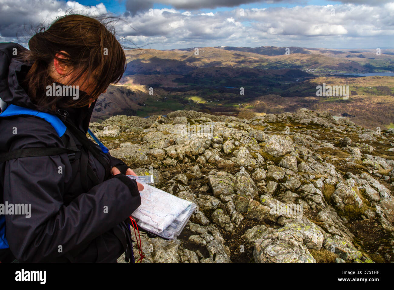 Woman hiker person taking a compass bearing from a paper map in the mountains, Old Man of Coniston horseshoe, Lake - Stock Image