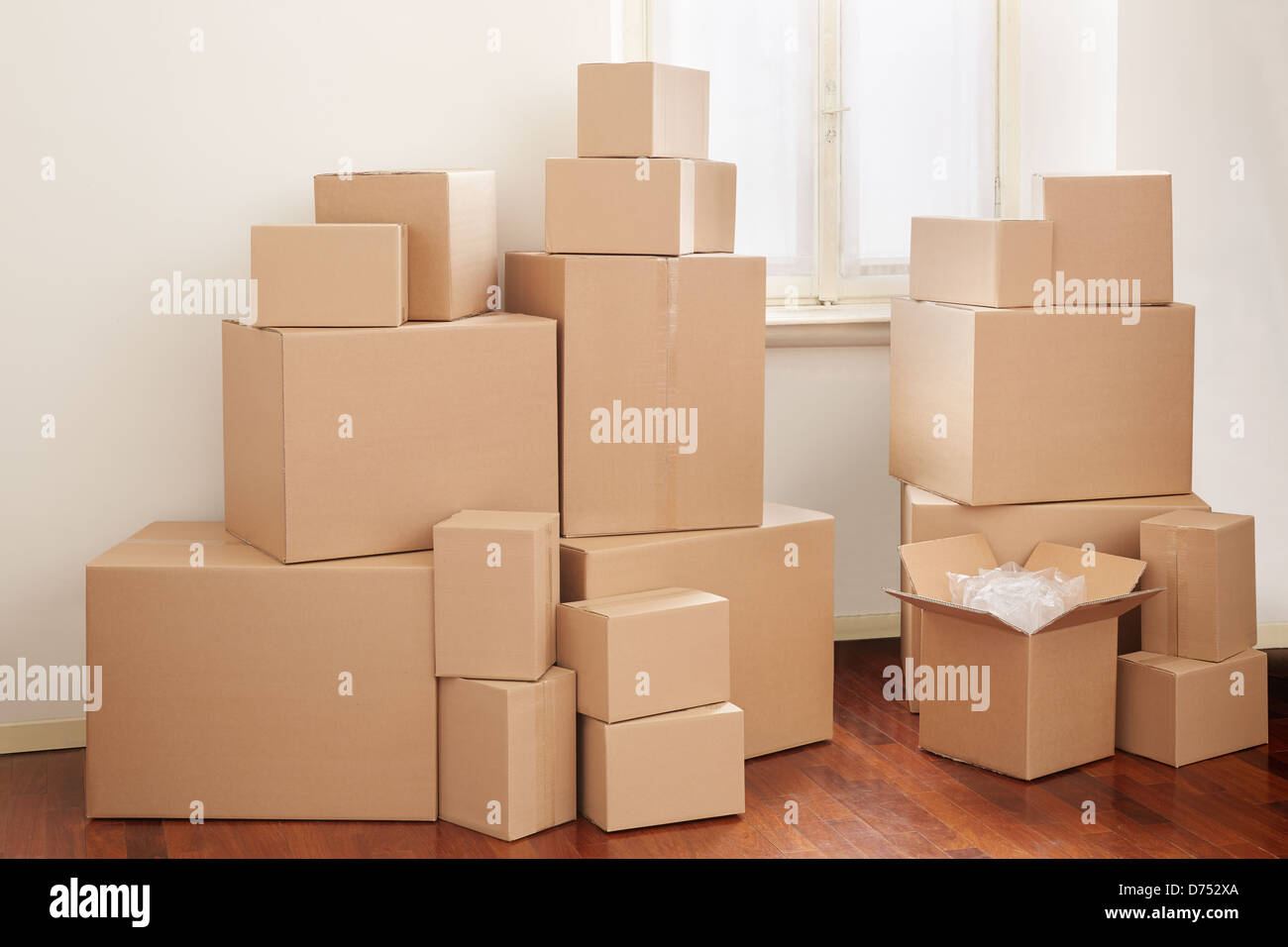 Cardboard boxes in apartment, moving day - Stock Image
