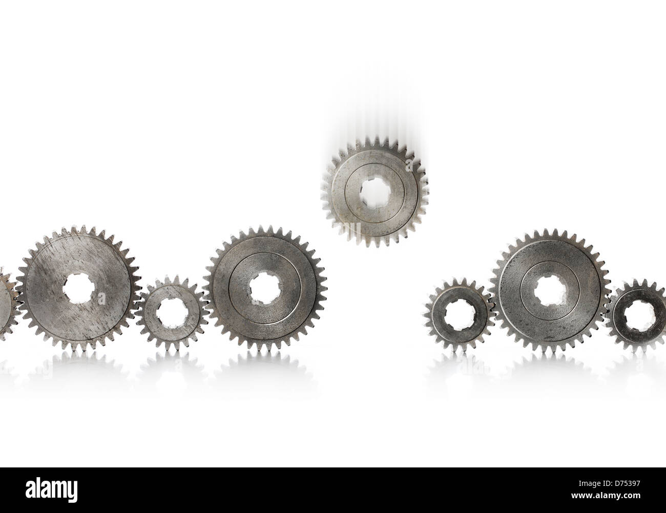 A row of old metallic cog gears being filled with one blurry falling gear. - Stock Image