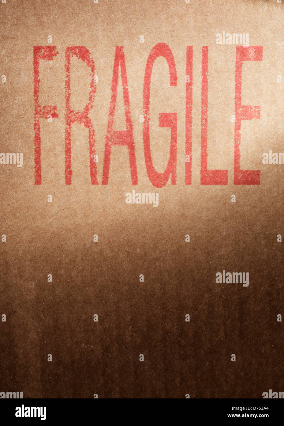 Closeup of a brown cardboard box with word 'Fragile' stamped with red ink. - Stock Image