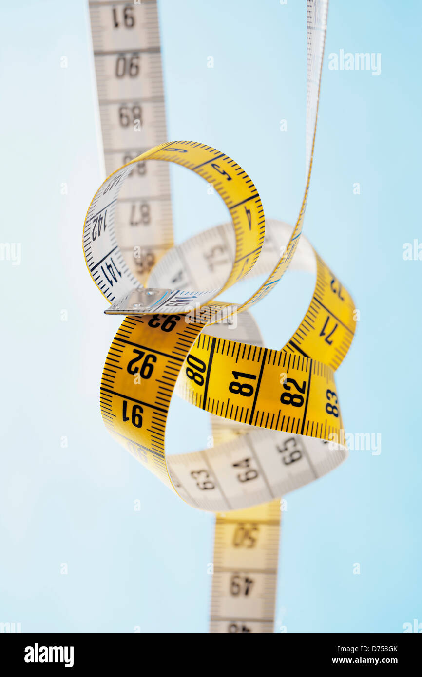 Tangled yellow and white metric tape measure. - Stock Image
