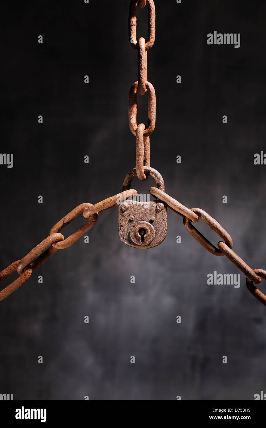 Old rusty lock holding three rusty chains together. - Stock Image