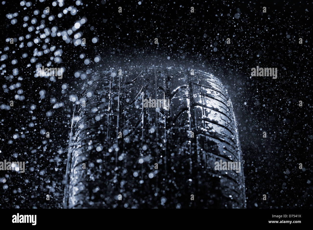Car tire in rainy conditions. Very short depth-of-field. Stock Photo