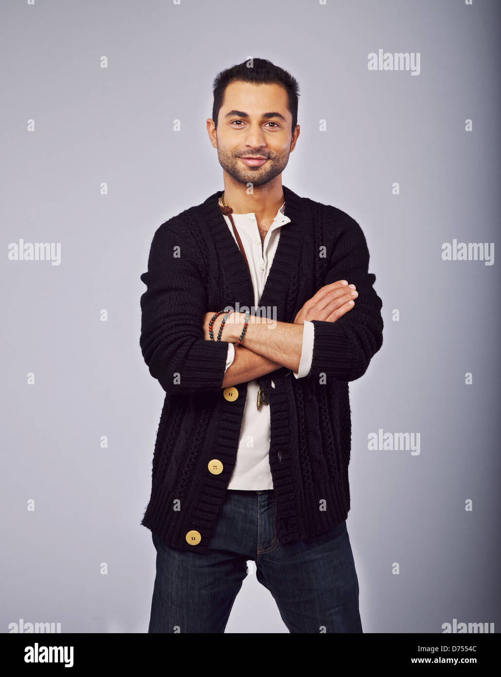 Portrait of a smiling fashionable guy standing in a studio - Stock Image