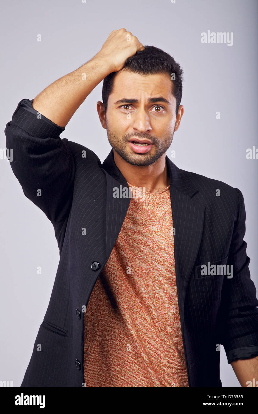 Man in a studio scratching his head in confusion - Stock Image