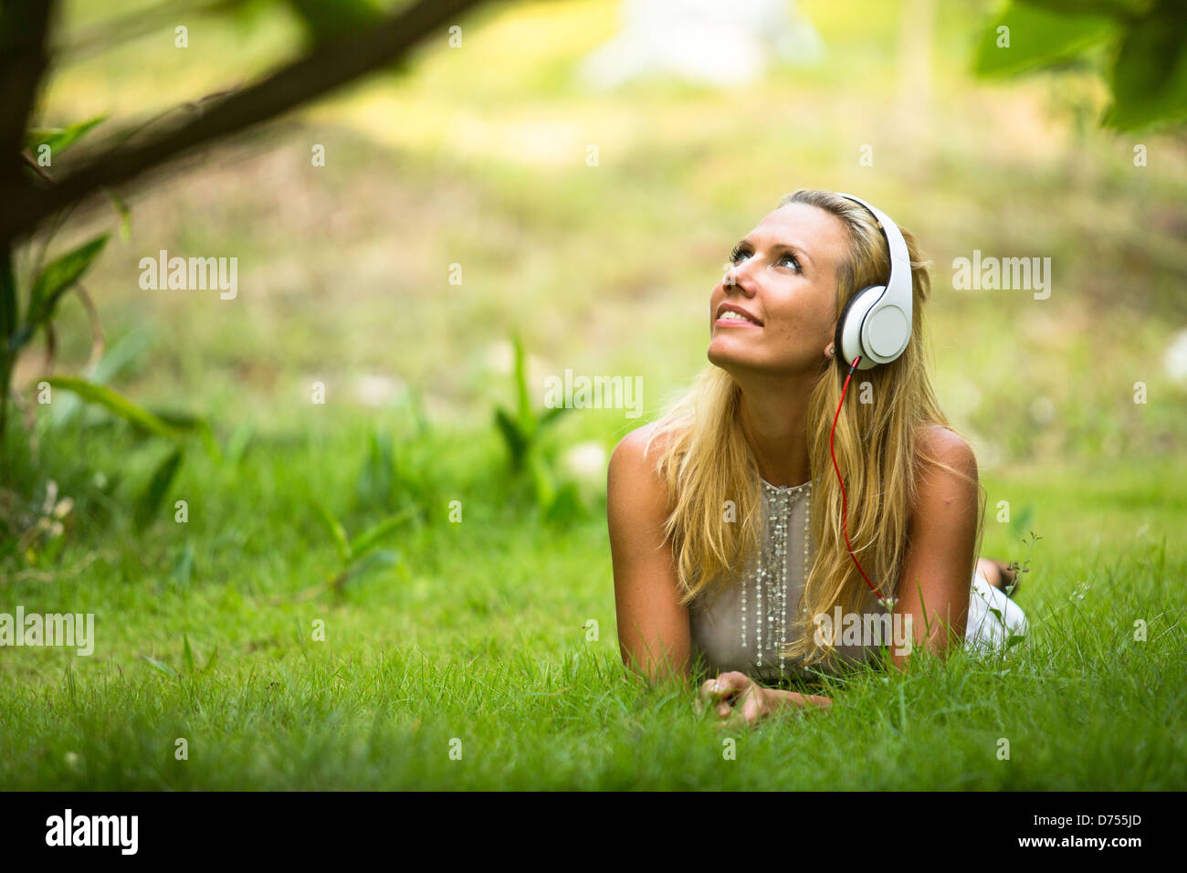 Lovely girl with headphones enjoying nature and music at sunny day. - Stock Image