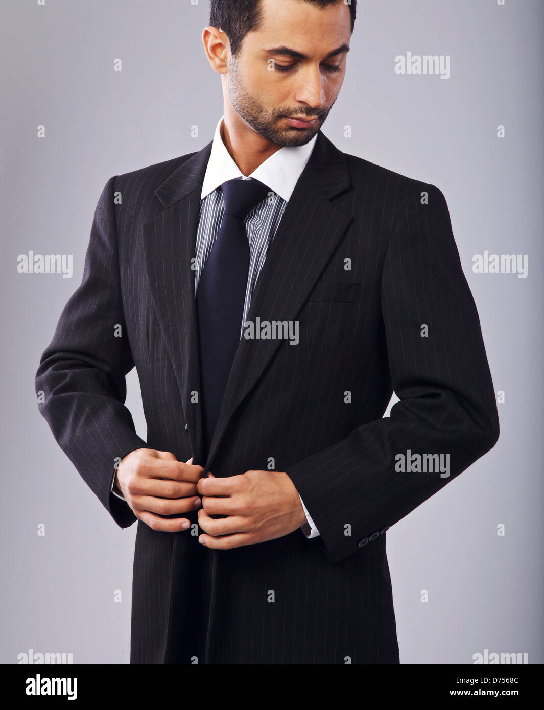 Portrait of a stylish businessman buttoning his suit - Stock Image