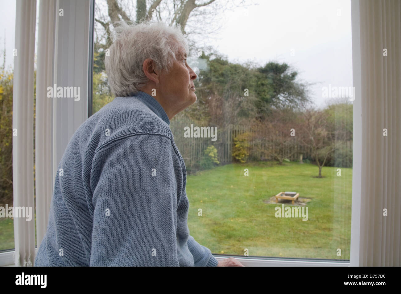 UK Elderly woman staring out of conservatory window on a cold and wet day Stock Photo