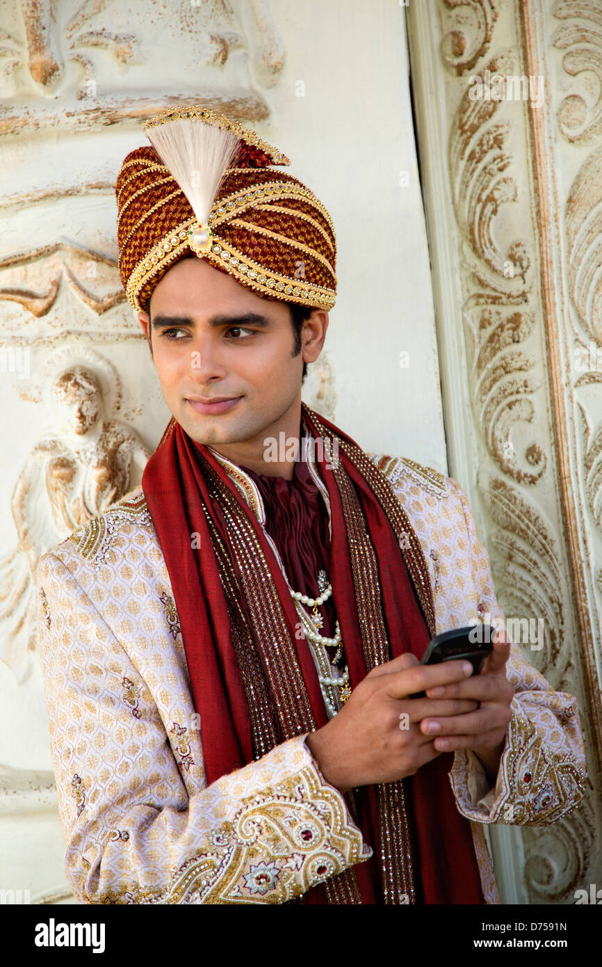 Indian groom in traditional wedding outfit and text messaging on a ...