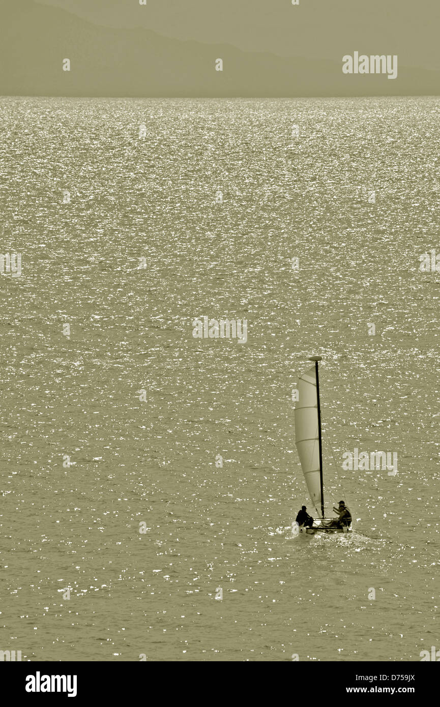 Small sail boat heading to the sea away from the shore - Stock Image