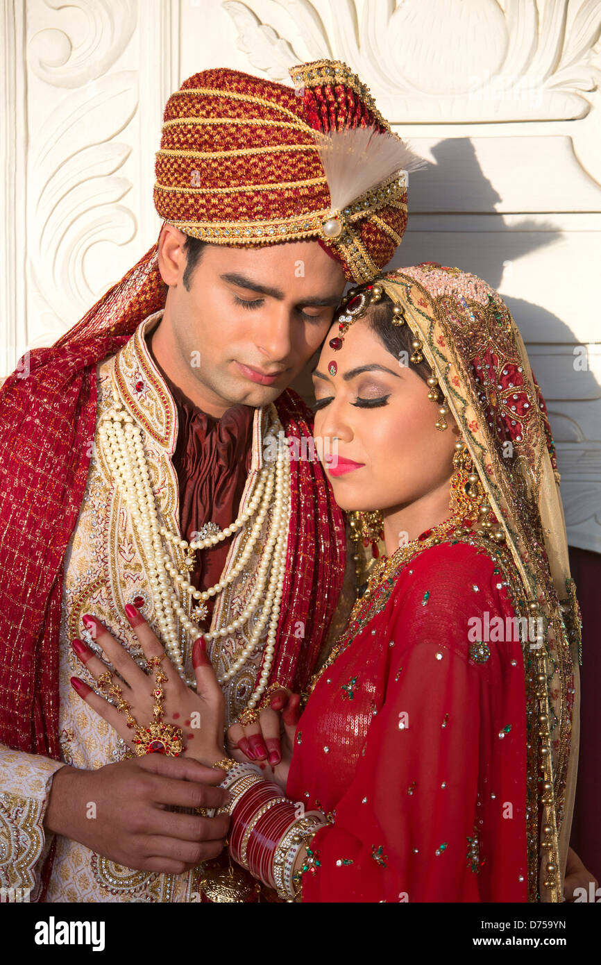 f653a456a2 Indian bride and groom in traditional wedding dress and hugging ...