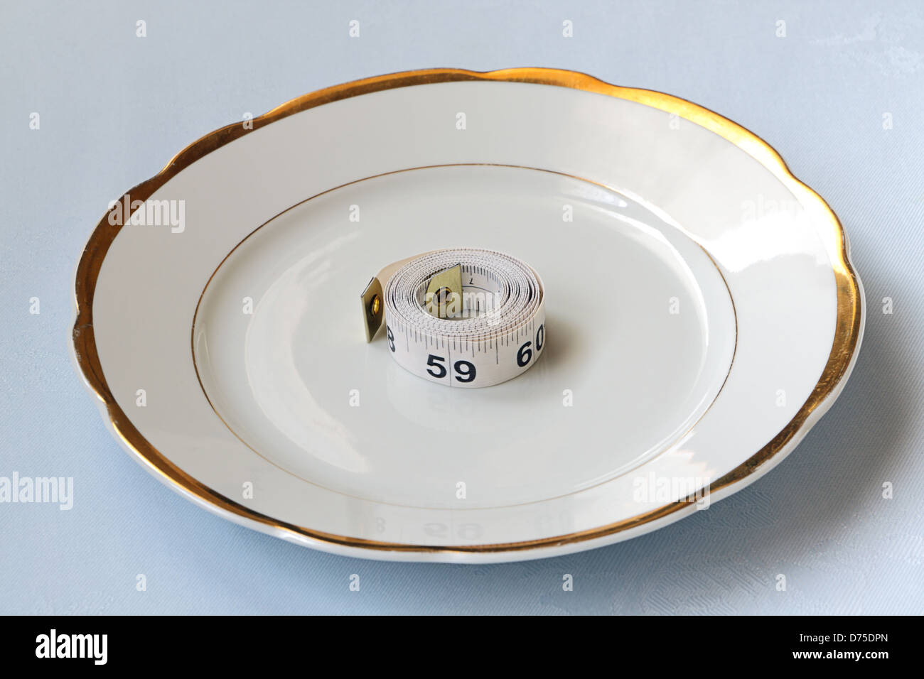Roll of white centimeter on white china ware - Stock Image