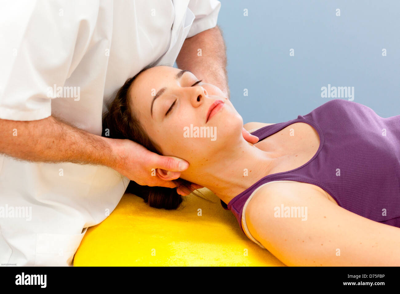 Craniosacral manipulations on a woman. - Stock Image