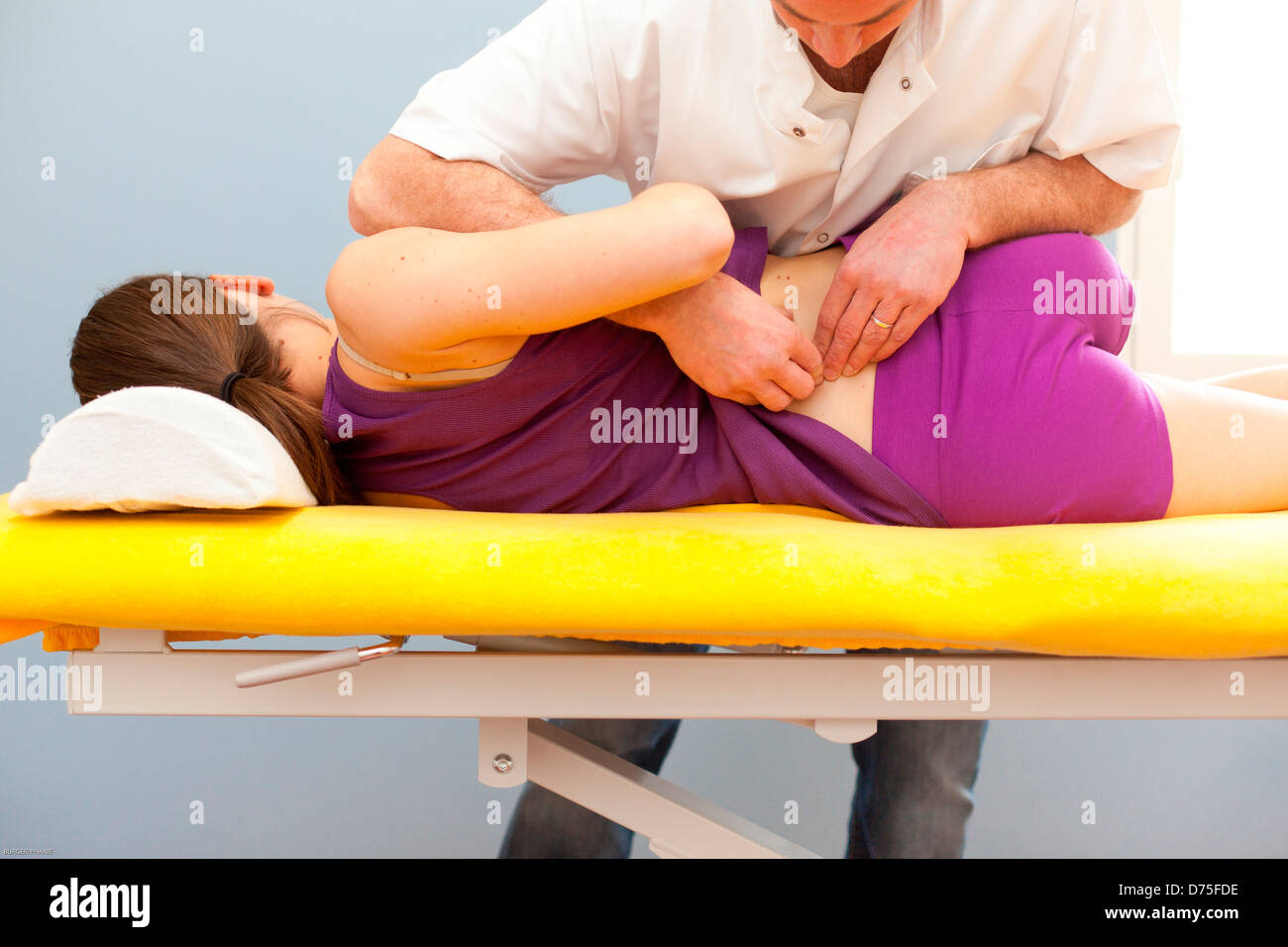 Structural osteopathy session on a woman with low back pain - Stock Image