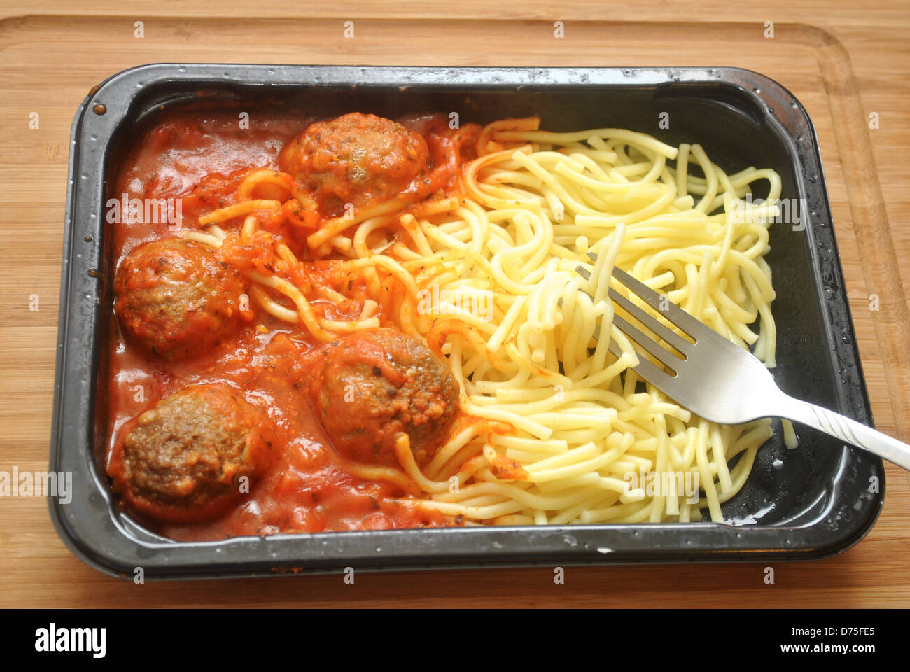 Eating a Spaghetti and Meatball TV Dinner - Stock Image